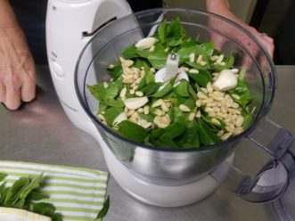 Basil, garlic, and pine nuts are initially coarse chopped in a food processor.