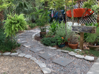 """This gravel pathway incorporates stepping stones to provide a more permeable walkway than a traditional concrete sidewalk."""